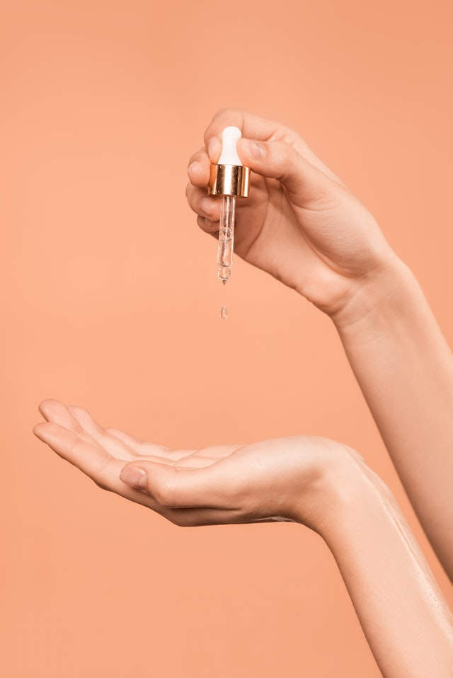 Person holding dropper with serum